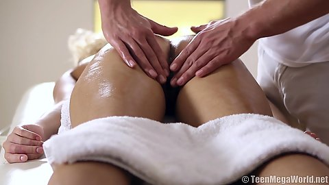 Naked Olivia C relaxing on massage table and getting pussy oiled