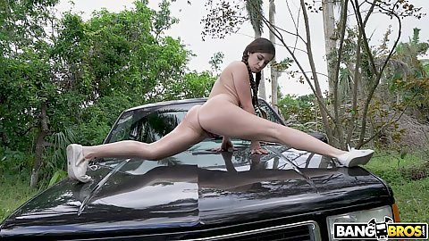Annika Eve doing some stretching moves on the hood of a car outdoors then squats for oral