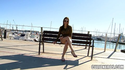 Outside by the marina on a bench with a view fully clothed sunglasses wearing little short girl Aletta Ocean awaits us to approach and flash