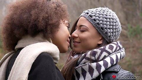 Two in love French and Brazilian girl Luna Corazon and Cassie Del Isla talka walk outdoors on a cold day and kiss in passionate