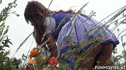 Sexy dress girl picking some flowers in the field Ginissima of Austria plays with a vibrator by a cottage