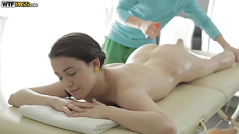 Salacious Izi Ashley relaxing naked on massage table as masseur rubs his hands with oil all over her bare body